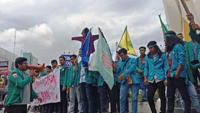 Para mahasiswa ketika melakukan aksinya di Bundaran Simpang Lima Banda Aceh, Senin (24/9/2018). (Foto/Ist)