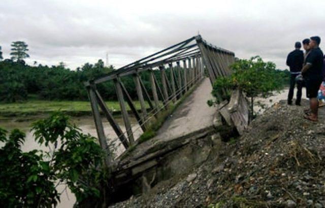 Warga melihat jembatan rangka baja yang ambruk di lintasan Meulaboh-Pante Ceureumen di kawasan Sawang Teubee, Kecamatan Pante Ceureumen, Aceh Barat. (Foto/Dedi Iskandar)