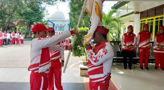 Bupati Pidie, Roni Ahmad alias Abusyik, mencium bendera Koni yang diserahkan Ketua Koni, Samsul Bahri, pada acara pelepasan kontingen Pora Pidie di Pendopo Bupati Pidie, Jumat (16/11/2018). (Foto/Muhammad Riza)