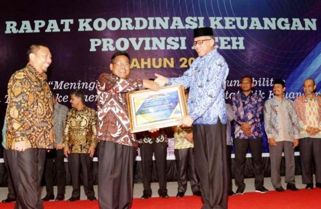 Plt Gubernur Aceh, Ir Nova Iriansyah, ketika menyerahkan penghargaan WTP kepada Wali Kota, Aminullah Usman, di Gedung Amel Convention Center Banda Aceh, Kamis (29/11/2018). (Foto/Ist)