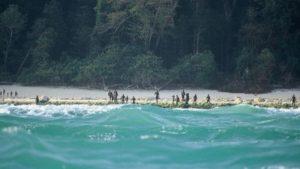 Sekelompok suku terasing di Pulau Sentinel Utara terlihat berjaga-jaga di pinggir pantai pulau itu pada 2005. (Christian Caron - Creative Commons A-NC-SA)