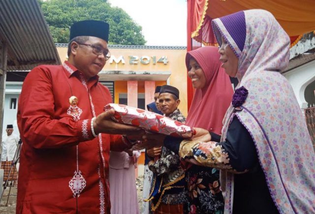 Bupati Aceh Barat, H Ramli MS, menyerahkan bantuan puluhan mukena, sajadah dan Alquran kepada masyarakat di sela-ela pencanangan Kampung Muslimin yang dipusatkan di Desa Paya Baro, Kecamatan Woyla Timur, Kamis (6/12/2018). (Foto/Dedi Iskandar)
