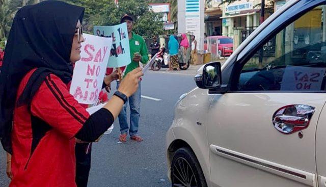 Seorang wanita petugas Dinas Kesehatan Pidie dari Puskesmas Padang Tiji sedang membagi-bagikan stiker bertuliskan Say No HIV/Aids kepada warga. Kegiatan itu bagian dari peringatan hari HIV/AIDS sedunia setiap 1 Desember. (Foto/Muhammad Riza)