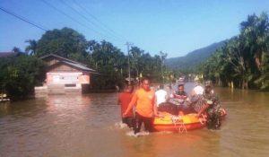 Tim gabungan membantu menyeberangkan warga memamakai perahu karet untuk melintasi genangan air di ruas Jalan Nasional, Desa Ladang Rimba, Trumon Tengah, Aceh Selatan, Minggu (16/12/2018). (Foto/Ist)