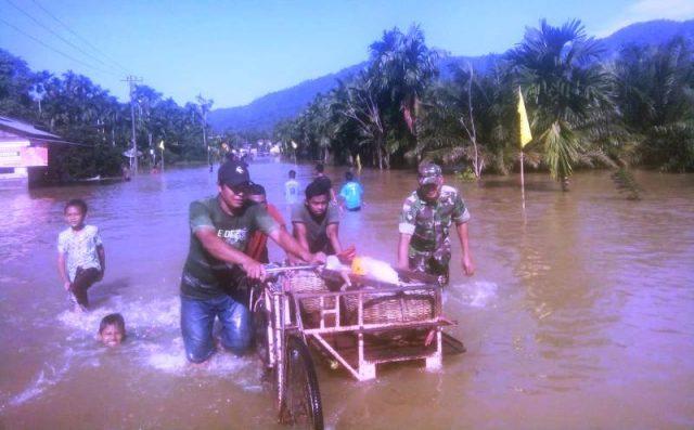 Petugas terlihat membantu warga melintasi jalan yang direndam banjir di Aceh Selatan. (Foto/Ist)