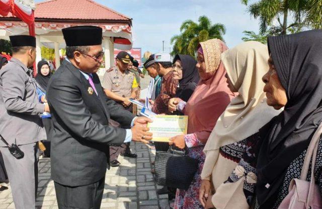 Bupati Aceh Barat, H Ramli MS menyerahkan bantuan voucher listrik gratis bagi 6.893 kepala keluarga yang berasal dari keluarga kurang mampu, Senin (17/12/2018). (Foto/Ist)