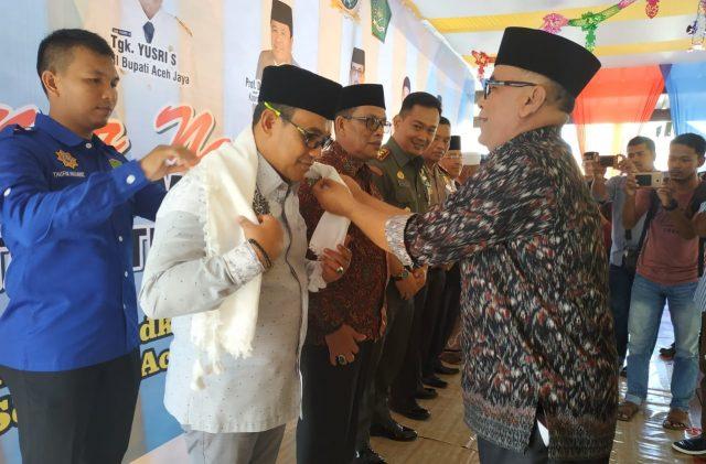 Pemasangan selempang kepada Bupati Aceh Jaya, H.T.Irfan TB, oleh Ketua Yayasan Pendidikan Dayah Terpadu Baitul Makmur Krueng Sabee pada acara lauching kampus STAI-PTQI. (Foto/Zammil)