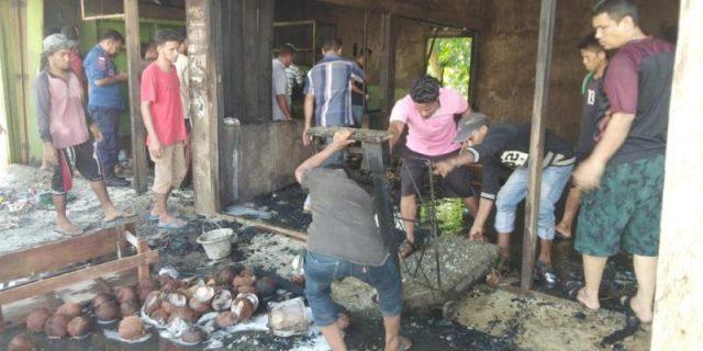 Warga terlihat sedang membantu menyelamatkan barang-barang yang masih bisa digunakan dari dalam dua kios yang terbakar di Gampong Teubeng Tanjong, Pidie, Kamis (3/1/2019). (Foto/Muhammad Riza)